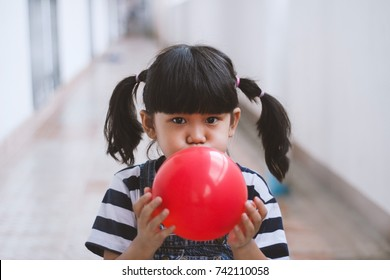 Little girl blowing up red balloons happy and funny at home