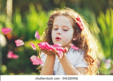 Little girl blowing rose petals from her hands. Fresh, healthy respiration concept.