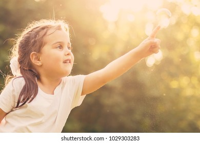 little girl blowing soap bubbles with her grandmother outdoors