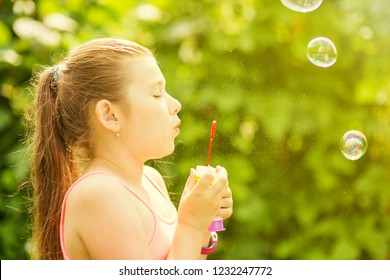 Little girl blowing soap bubbles in the park