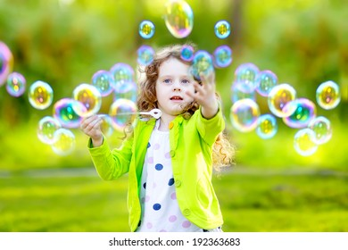 A little girl blowing soap bubbles, closeup portrait.