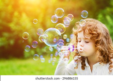 A little girl blowing soap bubbles in summer park. Background toninf for instagram filter.