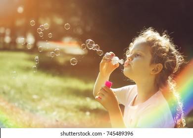 Little girl blowing soap bubbles in sunset light. Rainbow lens reflex.