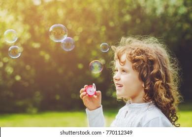 little girl blowing soap bubbles in summer park.