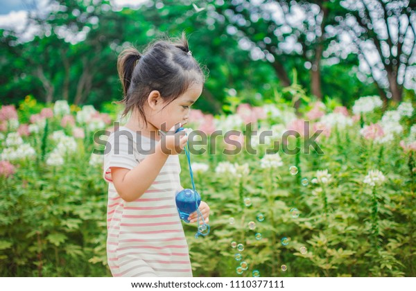 A little girl blowing soap bubbles in the park at sunny day. subject is blurred.