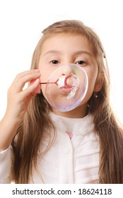 Little girl blowing soap bubbles.Isolated
