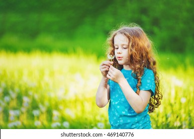 Little girl blowing white dandelion in meadow. Healthy, breathing, medical, allergy and happy childhood concept.