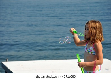 a little girl blows bubbles at the lake on a summer day