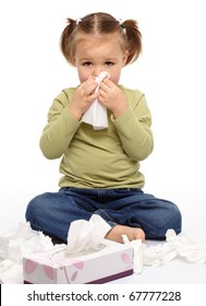 Little girl blows her nose while sitting on floor, isolated over white
