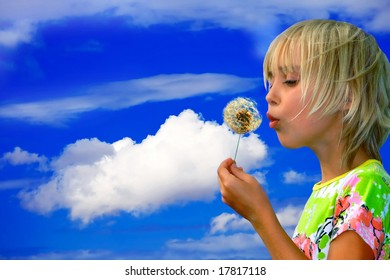 Little girl blows on a seedy pod plant as seeds drift off