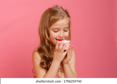 a little girl blows out a candle on a birthday cake in a Studio on a pink background