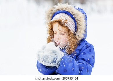 Little girl blows snow with mittens, on a snowflakes bokeh background.
