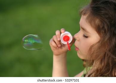 Little girl blows soap bubble