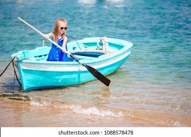 Little girl in blue boat in the sea bay in Greece. Little kid enjoy swimming in the small boat.
