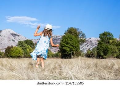 Little girl in blue dress dancing on the meadow