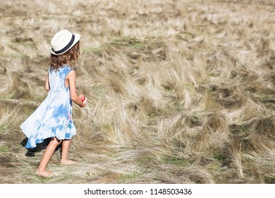 Little girl in blue dress holding an apple and having a walk in the field
