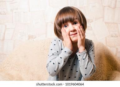 A little girl with blue eyes fools around. Children's dentist. Go to the dentist. Children's portrait.