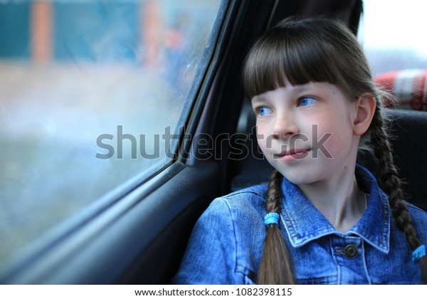 little girl with blue eyes sitting in the back of the car at the window
