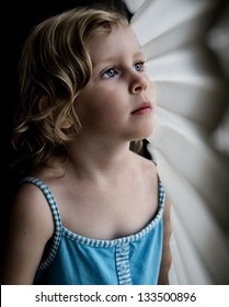 Little girl with blue eyes wearing blue dress gazing out window