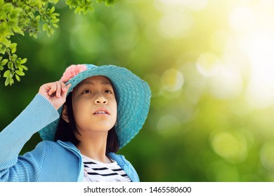 little girl in blue hat with nature background