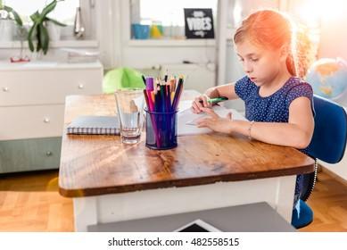 Little Girl in blue shirt doing homework on old wooden desk and using ruler