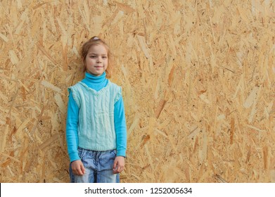 Little girl in blue sweater stands near plywood wall.