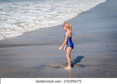 Little Girl in Blue Swim Suite Playing in Ocean Waves at the Beach