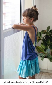 little girl in a blue top and blue skirt looks thoughtfully out the window