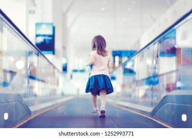 Little girl with blue toy running down the escalator in international airport terminal.