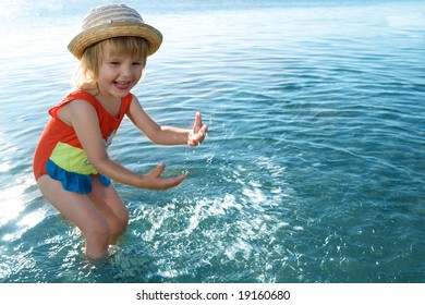 little girl in blue water sea  splashes