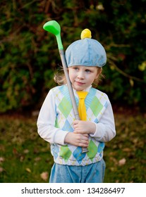 Little girl in blue yellow and green golfers clothes and hat, holding plastic golf club and looking into distance