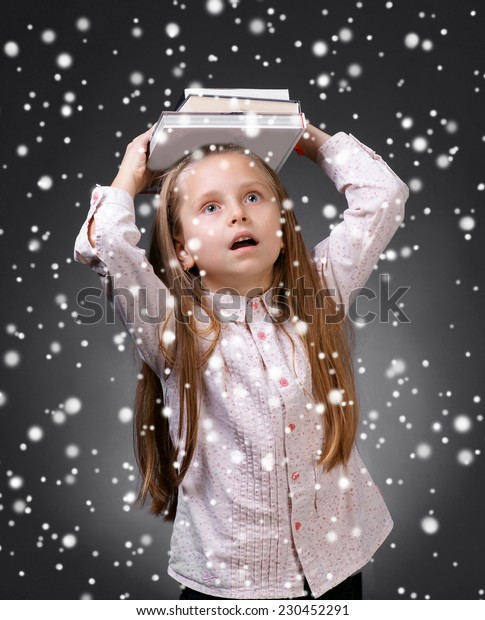 Little girl with books. Christmas and holidays concept
