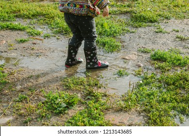 little girl in boots trampling a muddy puddle in autumn