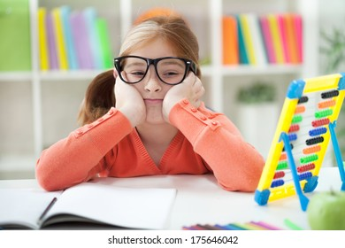 A little girl bored with her homework.