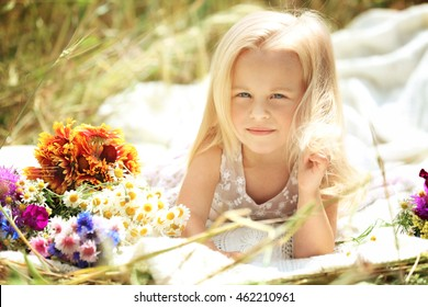Little girl with bouquet of flowers in the field