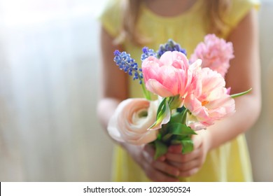 Little girl with bouquet of spring flowers in her hands. Mothers day concept