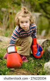 Little girl in boxing gloves playing in garden. Long Shot. LS.