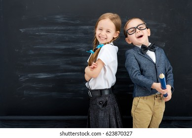 Little girl and boy against blackboard. School concept