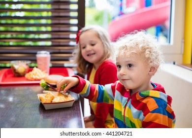 Little girl and boy eating chicken nuggets, hamburger and French fries in a fast food restaurant. Child with sandwich and potato chips. Kids eat unhealthy fat food. Fastfood sandwich for children.