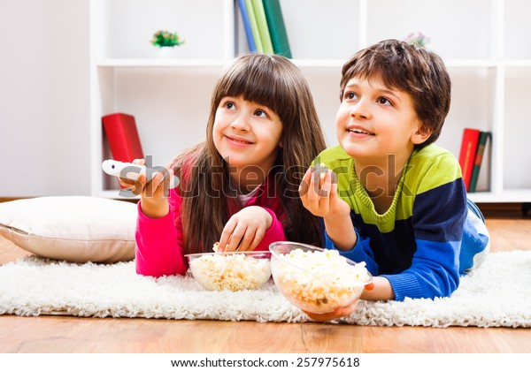 Little girl and little boy enjoy eating popcorn and watching tv at home.Leisure time for children