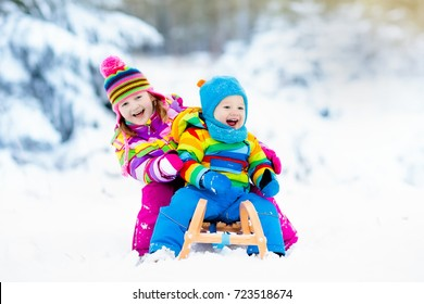 Little girl and boy enjoy a sleigh ride. Child sledding