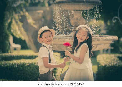 Little girl and boy  enjoy in wedding dress in garden with old classic style stone fountain with flowing water concept for valentine day in vintage tone
