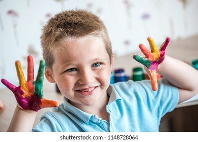little girl and boy hands painted in colorful paints.