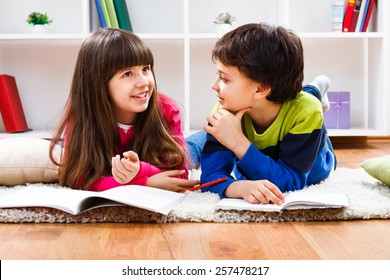 Little girl and little boy have decided to take a break from homework and now they are having conversation.Children talking