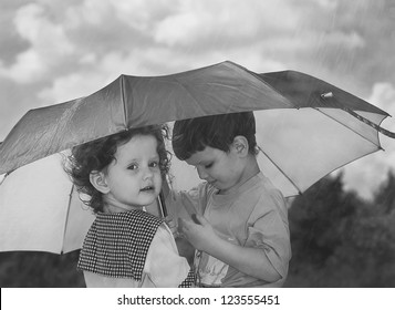 little girl and boy hiding under an umbrella from the rain, black and white photo