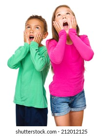 Little girl and boy are holding their faces in astonishment while looking up, isolated over white