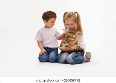 little girl and boy hug the cat