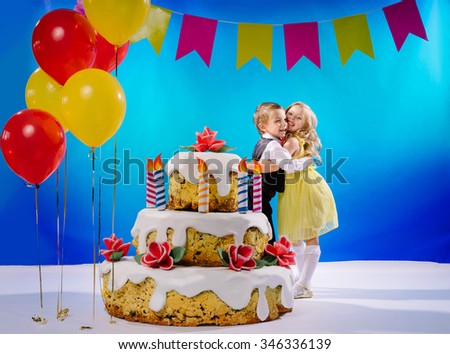 Little Girl And Boy Hugging Each Other Near A Big Birthday Cake With Candles