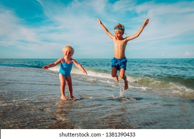 little girl and boy jump on beach, kids enjoy vacation at sea