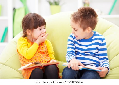 Little girl and boy laughing while reading from books
